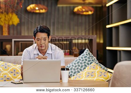 Pensive Young Vietnamese Businessman Sitting At Cafe Table With Opened Laptop And Reading E-mails An