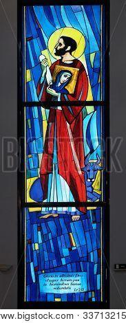 ZAGREB, CROATIA, SEPTEMBER 14, 2019: Saint Luke the Evangelist, stained glass window in the Church of Saint Benedict in Micevec, Zagreb, Croatia