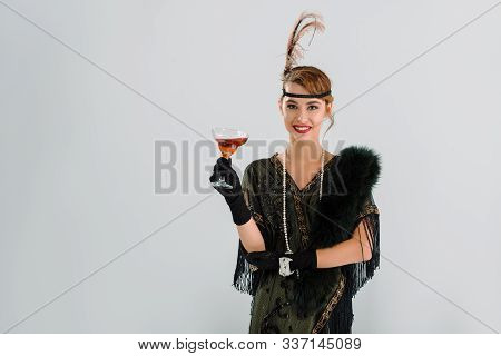 Cheerful Aristocratic Woman Holding Glass With Alcohol Drink Isolated On Grey