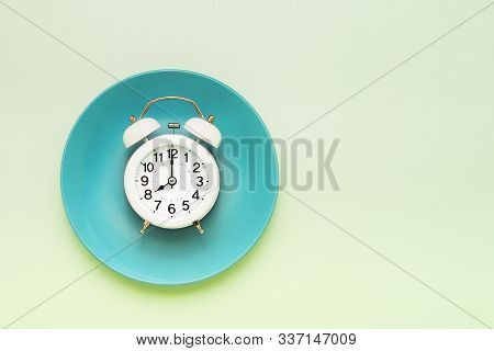 Intermittent Fasting Concept. White Alarm Clock On Empty Green Plate. Top View, Copy Space.
