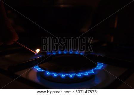 Gas Burner On White Modern Kitchen Stove. Kitchen Gas Cooker With Burning Fire Propane Gas. A Man Li