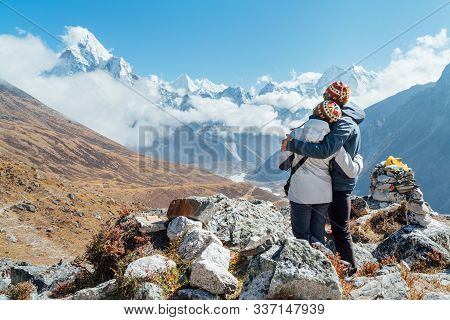 Embracing Couple Having A Rest On Everest Base Camp Trekking Route Near Dughla 4620m. Backpackers Le