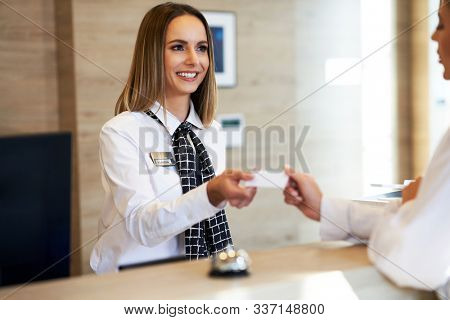 Receptionist giving key card to businesswoman at hotel front desk