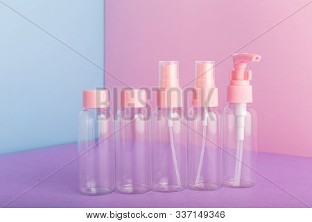 Plastic bottles for packaging hygiene products, homemade natural cosmetics, travel kit toiletries.Bottle, jar set on color pink background. Cosmetic package collection for cream, soaps, shampoo. Mock up poster