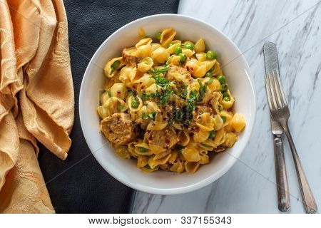 Sausage Macaroni And Cheese With Green Peas In Bowl On Marble Kitchen Table