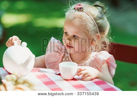 Little Girl Having A Tea Party In The Backyard
