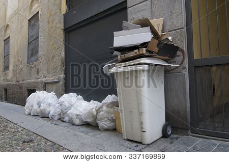 View Of A White Plastic Container Overfilled With Cardboard Waste And Many White Rubbish Bags Laying