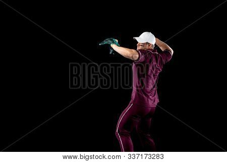 Side view of a Caucasian male baseball player, a pitcher or fielder, wearing a team uniform, baseball cap and a mitt, throwing a baseball