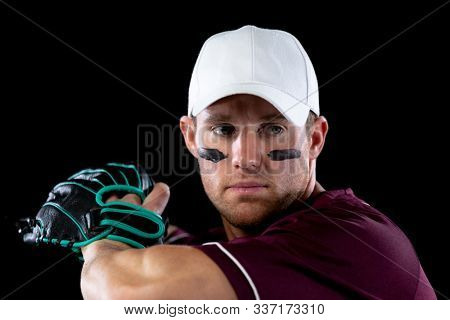 Front view close up of a Caucasian male baseball player, a pitcher wearing a team uniform, baseball cap and a mitt, preparing to throw a pitch, stripes of eye black under his eyes
