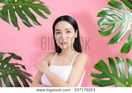 Natural Cosmetics. Sensual Asian Woman Against Tropical Leaves, Looking At Camera On Pink Background