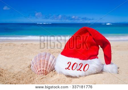 2020 Happy New Year Background With Santa Claus Hat And Seashell On The Tropical Beach Near Ocean In