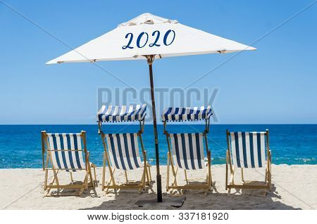 Symbol From Number 2020 On The Beach Umbrella With Chairs Near Ocean