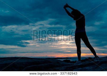 Silhouette Woman Workout In The Morning At Stone Beach With Beautiful Sunrise Sky. Fit Woman Stretch