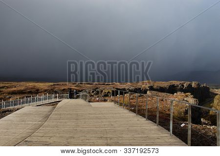 Golden Circle, Iceland -hazy sun through storm clouds at the boardwalk of Thingvellir National Park in Iceland poster