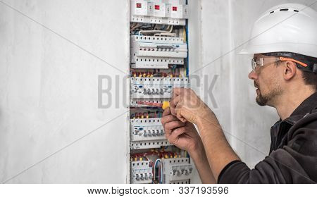 Man, An Electrical Technician Working In A Switchboard With Fuses. Installation And Connection Of El