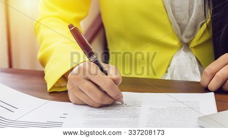 Business Women In Yellow Suite Use Pen Sign The Signature Of Consent In The Contract Agreement Docum