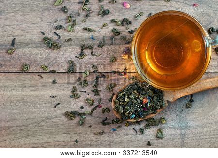 Blended Tea. Green Tea With Dry Flower Petals. Dry Leaves Of Green Tea In A Wooden Spoon And Glass C