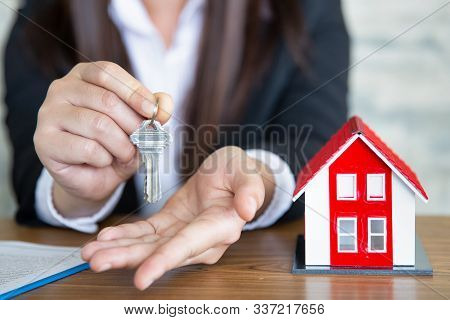 Business People Hold Home Keys And There Is A Red Roof House Near The House Selling Concept, Will Gi