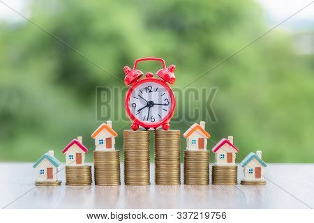 Small House On The Coin Ladder With A Red Alarm Clock On The Coin Ladder. Investment Concepts. Finan
