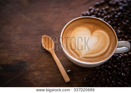 A Hot Coffee Cup With A Heart In The Coffee Cup With A Spoon Placed Near The Coffee Bean Roasted On