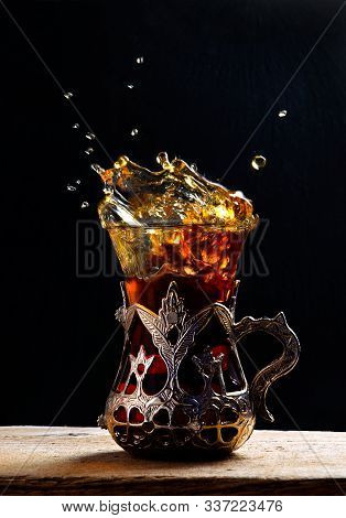 Turkish Tea In The Glass On The Table. Eastern. Tea Splashes. Splashing Turkish Tea In Traditional T