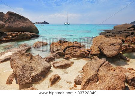 Similansky islands, Andaman Sea, Thailand. The thinnest white sand of a beach adjoins with huge brown rocks and azure water.