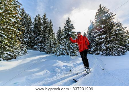 Woman cross country skiing on a sunny winter morning in Swiss Alps, Thyon, les collones, Valaise canton.