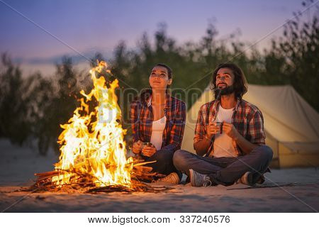 Tourist Couple Camping Near Campfire Outdoors On The Nature