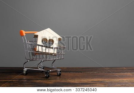 Building With A Heart In A Shopping Cart. The Concept Of Buying A House Or Apartment. Affordable Hou