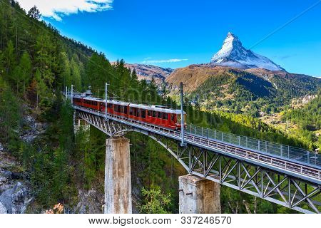 Zermatt, Switzerland. Gornergrat Red Tourist Train On The Bridge And Matterhorn Peal Panorama In Swi