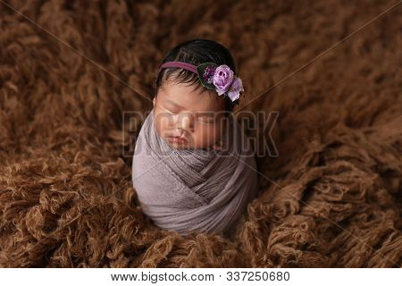 Portrait Of A Little Cute Newborn Asian Girl On Brown Fur. First Photo. Headband Decoration.