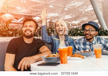Happy Young Woman Waving Hand And Sitting Near Optimistic Multiethnic Guys During Friends Meeting In