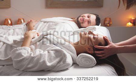 Charming Couple Enjoying A Head Massage In Modern Wellness Salon. Beauty Treatment Concept