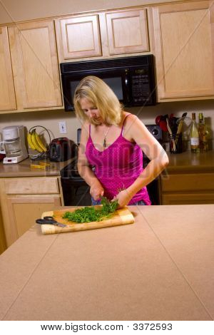Woman Chopping Food In The Kitchen