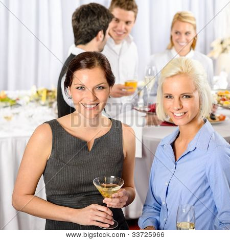 Two business woman smiling at catering buffet company meeting