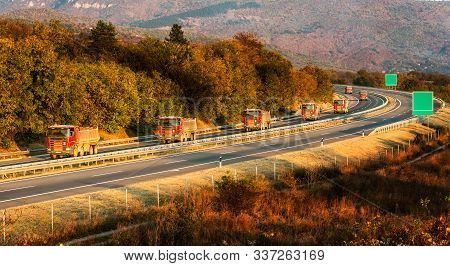 Convoy Or Caravan Of Red Utility Trucks On A Highway. Highway Transportation With Red Utility Tracks