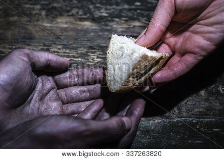 Hands Of A Girl Give Alms A Donation To The Dirty Working Hands Of A Man. On An Old Wooden Backgroun