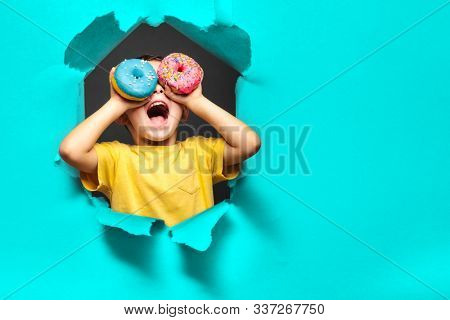 Happy cute boy is having fun played with donuts on black background wall. Bright photo of a boy. Colored donuts