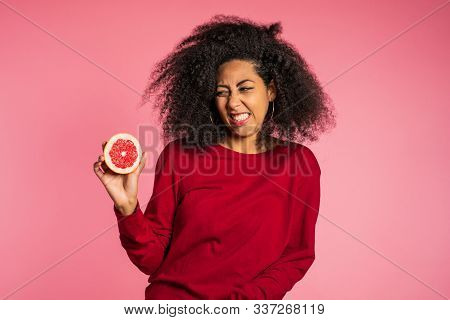 African American Girl Act Ape Her Face From Grapefruit Cid. Woman Grimaces. Lady With Curly Hairstyl