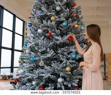 Woman Decorating Chirstmas Tree At Cozy Home