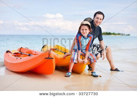 Happy father and son after kayaking relaxing near boats