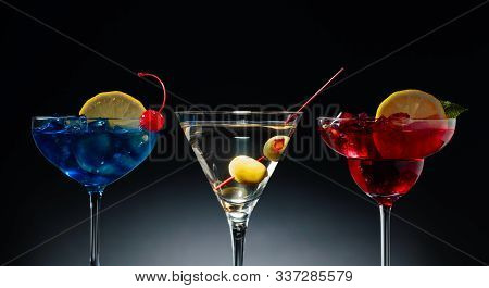 Two Colorful Cocktails And Dry Martini With Green Olives. Red And Blue Cocktails With Ice, Lemon, Mi