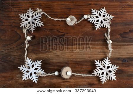 Christmas Decorative Snowflakes On Wooden Background  With Frame For Design.