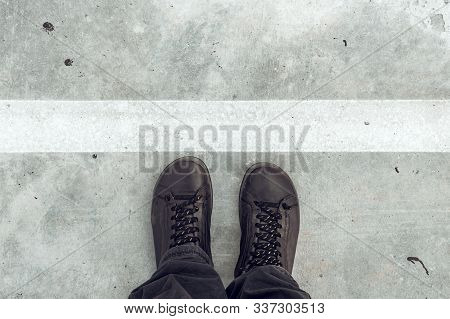 Standing At Dividing Line, Male Feet And Shoes From Above On Concrete Sidewalk With White Line As Bo