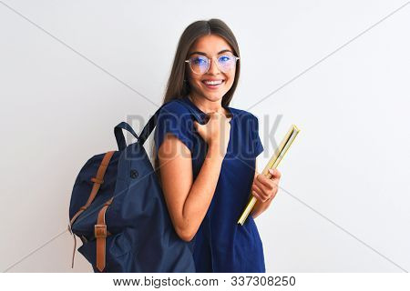 Young student woman wearing backpack glasses holding book over isolated white background with a happy face standing and smiling with a confident smile showing teeth