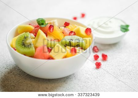 Bowl With Homemade Fresh Fruit Salad: Mango, Grapefruit, Pomegranate, Kiwi, Banana On A Light Backgr