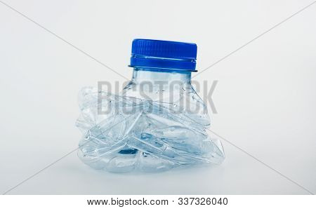 Closeup On Empty Trash Crushed Bottle Of Spring Water Isolated On White