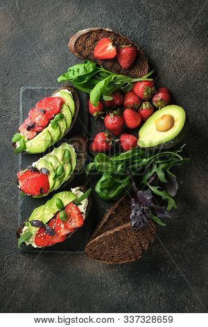Healthy Food. Vegan Breakfast. Bruschettas Or Toasts With Avocado And Strawberries On A Dark Backgro