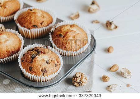 Vanilla Caramel Muffins In Paper Cups On White Wooden Background. Delicious Cupcake With Raisins, Al