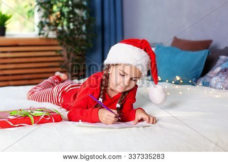 Merry Christmas. New Year 2020! Little Girl In Red Pajamas And Santa Hat Writes Letter To Santa Clau